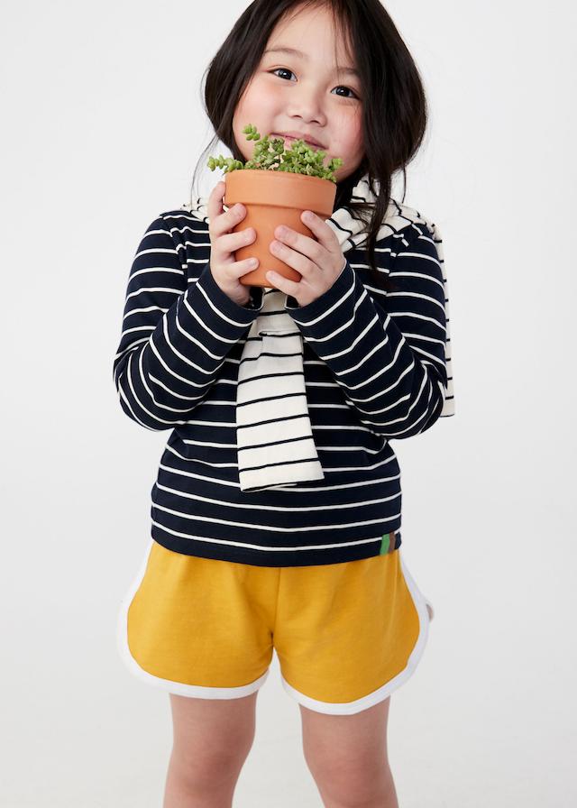 KULE Green - Smiling little girl holding a flower pot