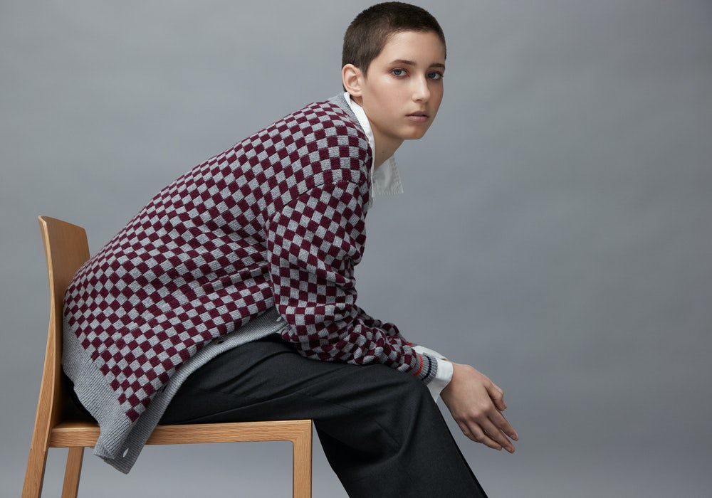 KULE - A male and female model standing back to back wearing classic Kule striped shirts, with several classic styles of Kule striped shirts draped over their shoulders.