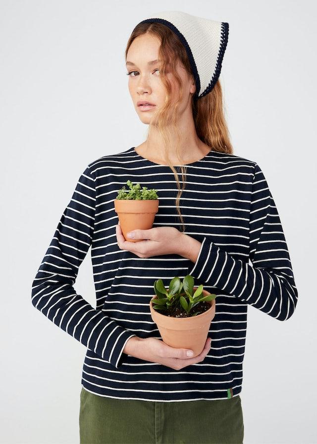 KULE Green - Model wearing The Modern Organic shirt holding two flower pots