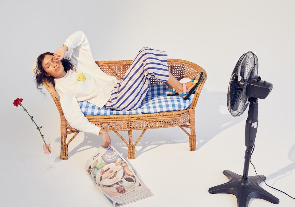 KULE Green - Model reclining on wicker lovesear wearing the oversized winky face sweatshirt in cream.