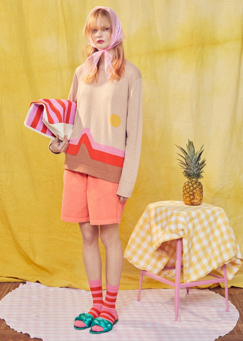 KULE- Model wearing The Lailani sweater, standing next to a block with a pineapple on top.