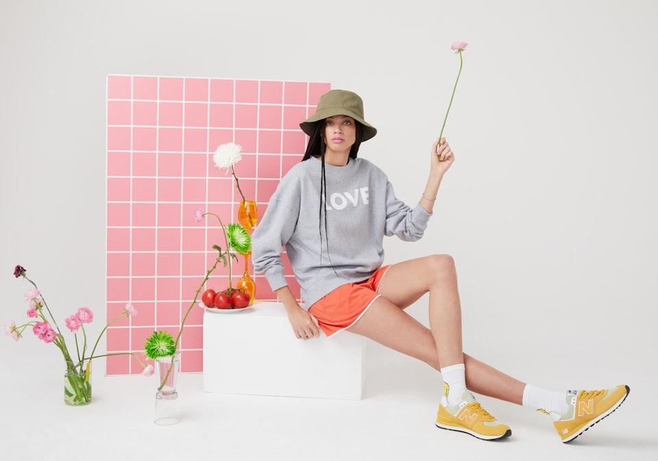 KULE Green - Model wearing LOVE organic cotton sweatshirt sitting on a block holding a pink flower