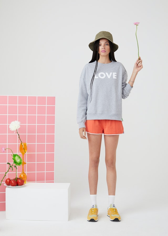 KULE Green - Model wearing LOVE organic cotton sweatshirt holding a pink flower next to a block with a flower in a vase and a plate of fruit