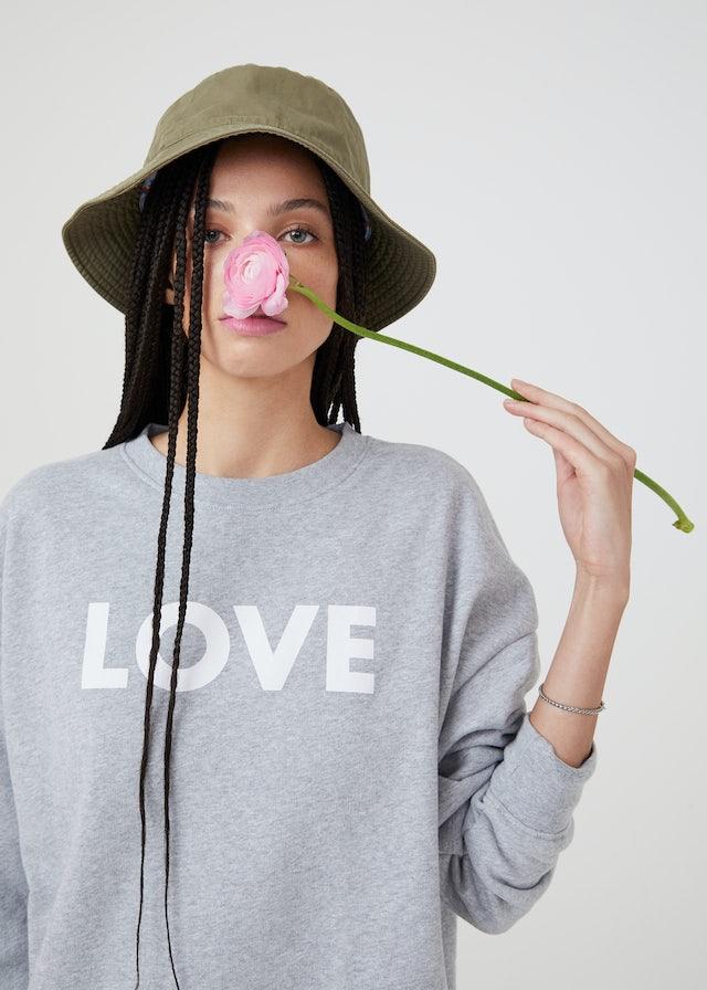 KULE Green - Closeup of model wearing LOVE organic cotton sweatshirt smelling a pink flower