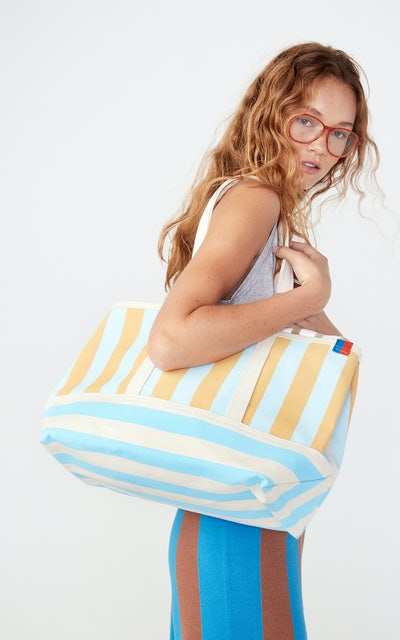 KULE- Model holding The Large Tote in blue/gold.