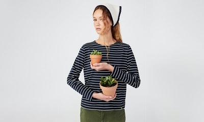 KULE- Model wearing The Organic Modern Long in Navy/Cream holding two small potted plants.