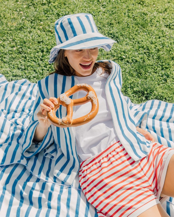 Model sititng on a beach towel in the grass wearing a hat and jacket from the LilyEve collection while eating a soft pretzle.